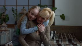Affectionate smiling girl embracing mother at home stock video footage