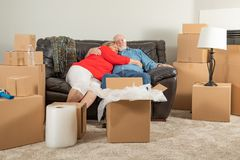 Affectionate Tired Senior Adult Couple Resting on Couch Surround. Ed By Moving Boxes royalty free stock images
