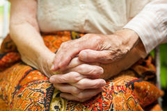 Affectionate touch of a caring husband. Elderly couple - the caring husband putting his hand on his wife's hands, showing love and support in hard times Royalty Free Stock Images