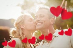 Affectionate woman kissing man. Composite image of red heart and affectionate woman kissing man on a sunny day stock photos