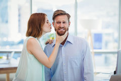 Affectionate woman kissing man. In office royalty free stock photography