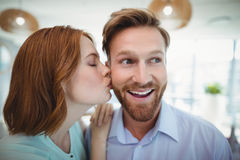 Affectionate woman kissing man. In office stock photography