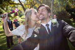 Affectionate woman kissing man during wedding. Affectionate women kissing men during wedding in park stock photo