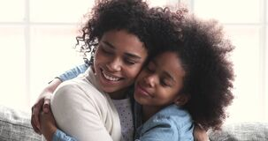 Affectionate young african american mommy cuddling happy biracial teen daughter.