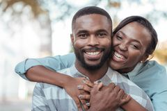 Affectionate young African couple standing outside on a sunny day. Smiling young African women hugging her husband from behind while standing together outside on stock photos