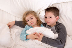 Affectionate young brother and sister lying in bed. Affectionate little brother and sister lying in bed cuddling together under the duvet looking up sleepily at Stock Photos