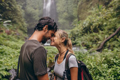 Affectionate young couple in forest. Shot of couple in love standing with their head together. Affectionate young couple in forest. Loving couple hiking in Royalty Free Stock Image