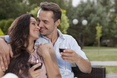 Affectionate young couple having red wine in park Royalty Free Stock Photography