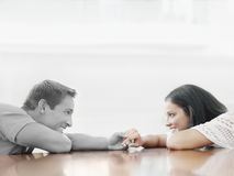 Affectionate young couple holding hands across table Stock Image