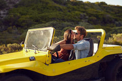 Affectionate young couple on a roadtrip. Man driving buggy car being kissed by his girlfriend Stock Photo