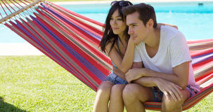 Affectionate young couple sitting on a hammock Royalty Free Stock Photos