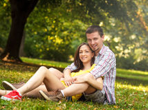 Affectionate young couple sitting in park Stock Photo