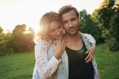 Affectionate young couple standing together in a park at dusk Stock Images