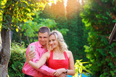 Affectionate young couple taking pictures using a smart phone Royalty Free Stock Images