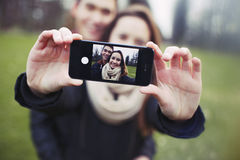 Affectionate young couple taking a self-portrait. With a smartphone at the park. Mixed race teenage men and women outdoors taking their picture with mobile Stock Image