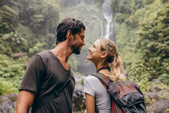 Affectionate young couple together on hike. Young men and women with backpack looking at each other and smiling. Hiking in forest with waterfall in background Stock Photo