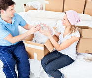 Affectionate young couple unpacking boxes at home Stock Photos
