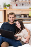 Affectionate young couple using a laptop Stock Images