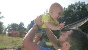Affectionate young father lifting cute baby boy up stock footage