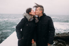 Affectionate young happy couple standing on pier by the sea and passionately kissing. Wonderful honeymoon Stock Images