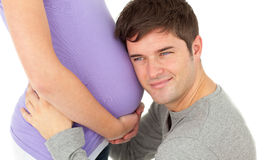 Affectionate young man listening to the belly Stock Photo