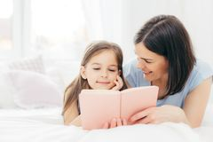 Affectionate young mother with dark hair, looks happily at her small daughter, read interesting book or fairy tale together, enjoy. Domestic atmopshere at home royalty free stock photos