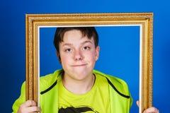 Affective nastoletni chłopak pozuje z obrazek ramą obrazy stock