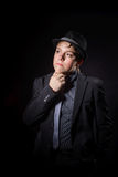 Affective teenage boy dressed in strong suit. Isolated on black background Stock Photography
