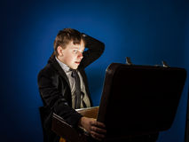 Affective teenage boy finding treasure in retro suitcase Royalty Free Stock Photography