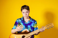 Affective teenage boy with guitar. Music concept. Stock Photos