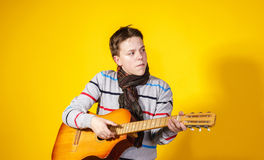 Affective teenage boy with guitar. Music concept. Royalty Free Stock Photo