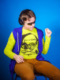 Affective teenage boy listening music in headphones. Isolated on blue background Stock Image