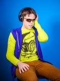 Affective teenage boy listening music in headphones Stock Photos