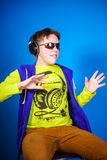 Affective teenage boy listening music in headphones. Isolated on blue background Stock Photos