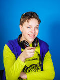 Affective teenage boy listening music in headphones. Isolated on blue background Stock Photo