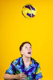 Affective teenage boy playing with ball. Isolated on yellow background Stock Photos
