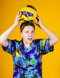 Affective teenage boy playing with ball Royalty Free Stock Photography