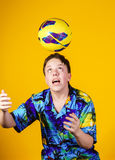 Affective teenage boy playing with ball Stock Photo