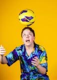 Affective teenage boy playing with ball Stock Photo