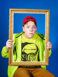 Affective teenage boy posing with picture frame Stock Photo