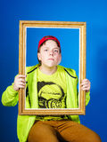 Affective teenage boy posing with picture frame Stock Photography