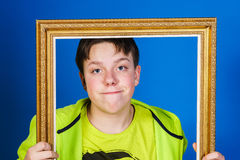 Affective teenage boy posing with picture frame Stock Images