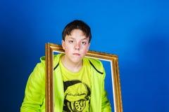 Affektiver Teenager, der mit Bilderrahmen aufwirft Stockfotografie