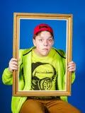 Affektiver Teenager, der mit Bilderrahmen aufwirft Stockfoto