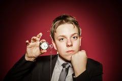 Affektiver Teenager mit der Uhr, die Zeit zeigt Lizenzfreie Stockfotos