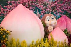 Affemaskottchen mit Pfirsich - Dekoration des Chinesischen Neujahrsfests Lizenzfreie Stockbilder