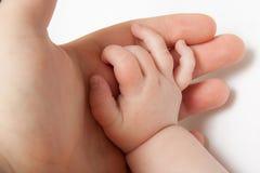 Afferrare la mano di un bambino Immagine Stock