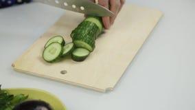 Affettare cetriolo per lattuga Taglio delle verdure sul bordo di legno della cucina stock footage