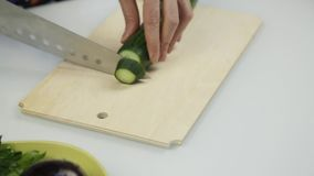 Affettare cetriolo per lattuga Taglio delle verdure sul bordo di legno della cucina archivi video