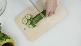 Affettare cetriolo per lattuga Taglio delle verdure sul bordo di legno della cucina Vista superiore 4K archivi video